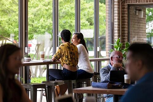 two customers chatting in a cafe while sitting on Tolix bar stools